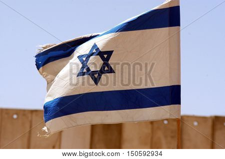 Israel national flag on the Israel-Gaza Strip barrier. The fence has kept Palestinians inside Gaza but has not stopped rockets being fired by militants into Israel.