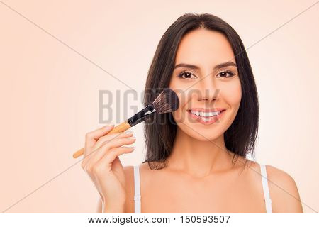 Happy Young Woman Holding Makeup Brush On Pink Background