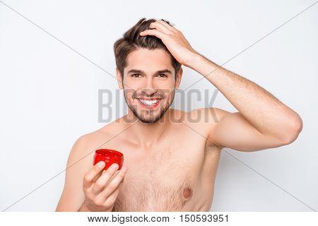 Cheerful Happy Young Man Applying Wax On His Hair