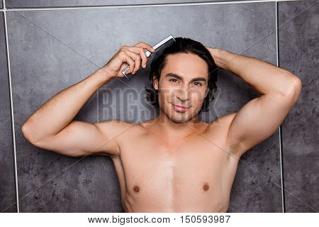 Portrait Of Handsome Strong Man Combing His Hair