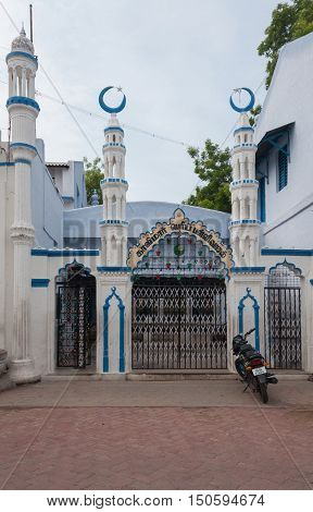 Madurai India - October 21 2013: Entrance with four short minarets to the Kajimar Mosque is painted white and blue. Black and white iron fence forms the gate