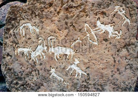 Rock drawings of hunting story on a carved stone in Timna Park, Israel.