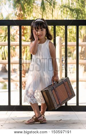 Smiling little girl with suitcase in a pretty dress.