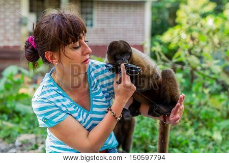 Close-Up Of Beautiful Young Woman With A Small Monkey On Her Shoulder That Stolen Her Sunglasses South America