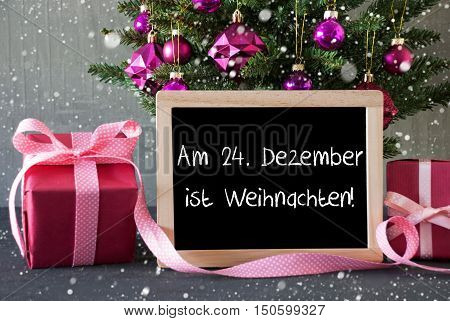 Chalkboard With German Text Am 24. Dezember Ist Weihnachten Means December 24th Is Christmas Eve. Christmas Tree With Rose Quartz Balls, Snowflakes.Gifts Or Presents In The Front Of Cement Background.