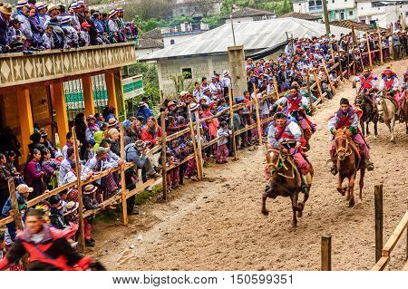 Todos Santos Cuchumatan, Guatemala - November 1 2011: Traditionally dressed locals watch drunken jockeys race up & down dirt track on horseback in unique All Saints' Day celebration in highland town