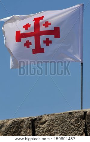 A Crusader flag of Jerusalem at Mount Tabor Israel. The cross of the Holy Land a Greek cross in red on a white background also known as the