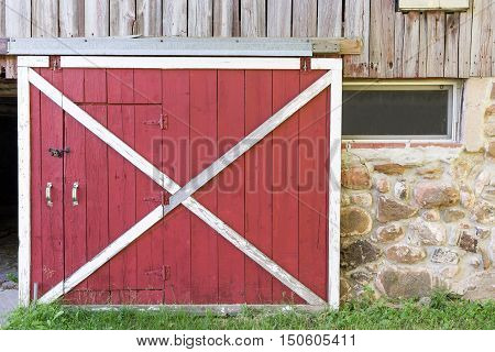 Partially open red barn door in a weathered barn. Traditional white framing weathered wood field stone texture and nostalgia.