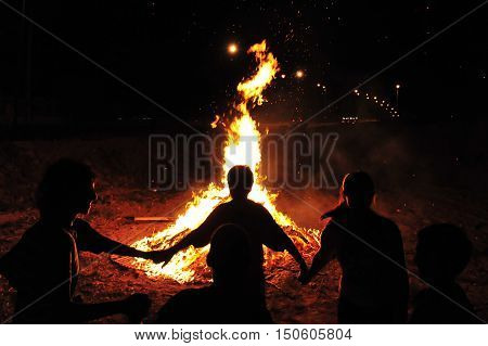 Israeli youth dance and celebrate by a bonfire the Jewish holiday of Lag Baomer by holding hands and dancing in a circle around a bonfire.