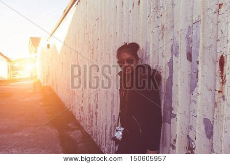 Young hipster woman with winter jacket against wooden wall. outdoor shot. soft retro vintage toned old image