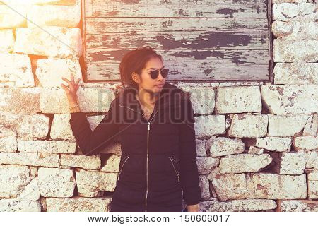 young woman in winter dress against old stone wall outdoor shot vintage and retro style