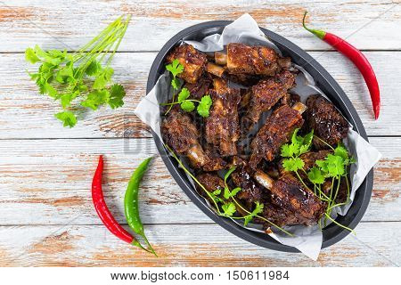 delicious hot sticky ribs seasoned with a spicy garlic ginger barbecue sauce amd cilantro in oval roasting Pan on white planks. green and red chili peppers on background view from above