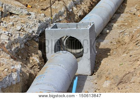 disconnected concrete drainage pipe sections lying in a ditch during new road construction, near Songkhla, Thailand