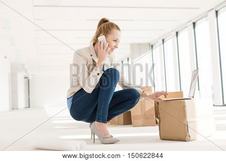 Full length of young businesswoman crouching while using mobile phone and laptop in new office