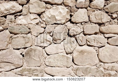 Old white rough stone wall. Background texture