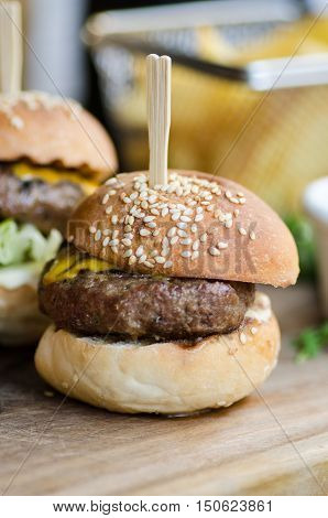 Small meat burger sliders on wooden table.
