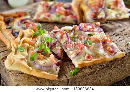 Hot baked tarte flambee from Alsace with onions, bacon and sour cream served on a shabby wooden cutting board poster