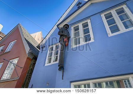 FLENSBURG GERMANY - OCTOBER 4 2016: Flensburg street Norderstrase with black man sculpture on blue gable holding red high-heeled shoes October 4 2016.