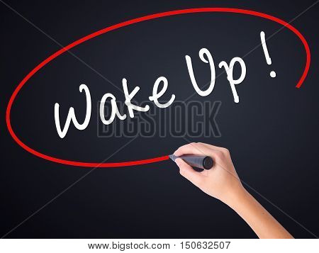 Woman Hand Writing Wake Up With A Marker Over Transparent Board