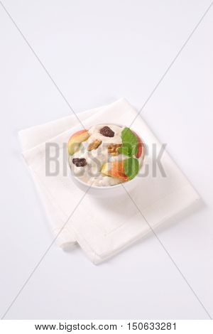 bowl of cream cheese with apples, nuts and raisins on white place mat