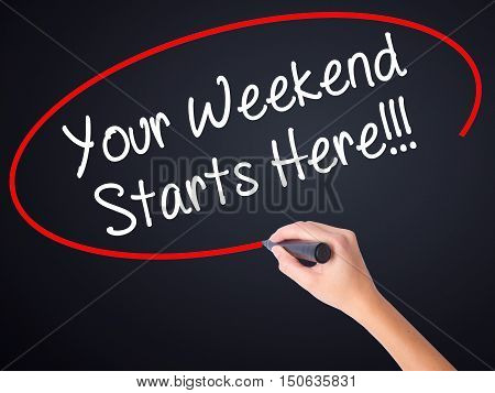 Woman Hand Writing Your Weekend Starts Here!!! With A Marker Over Transparent Board