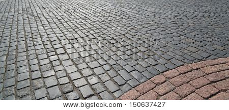 Abstract background of old cobblestone pavement close-up.