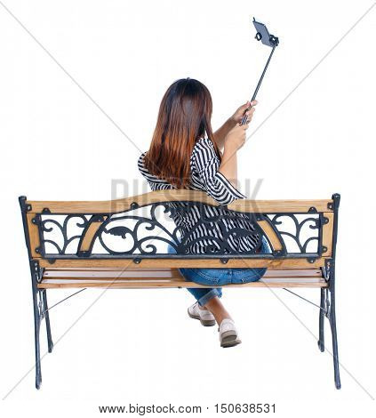 Back view of a woman to make a selfie stick portrait sitting on the bench. girl watching. Rear view people collection. backside view of person. Isolated over white background. girl sitting and