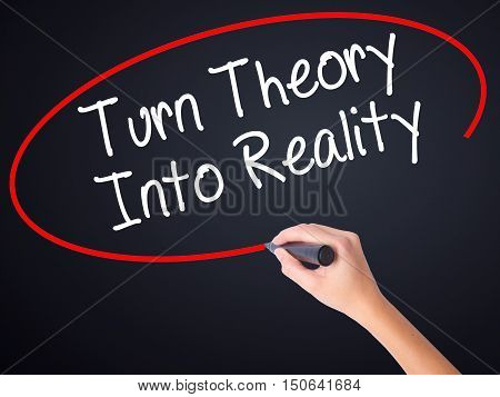 Woman Hand Writing Turn Theory Into Reality With A Marker Over Transparent Board