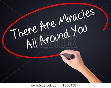 Woman Hand Writing There Are Miracles All Around You  With A Marker Over Transparent Board