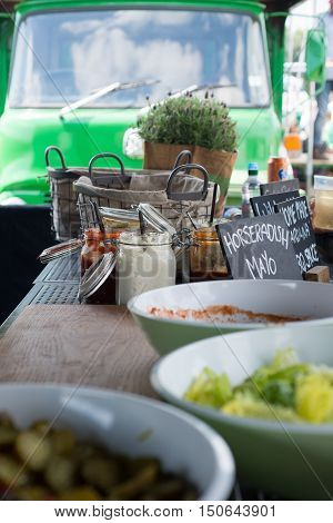 Bowls Of Food And Jars Of Sauce On A Table With A Truck In The Background