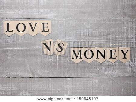love vs money paper letters symbol motivation sign on wooden board