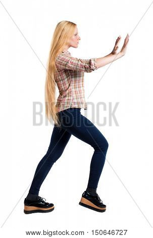 back view of woman pushes wall.  Isolated over white background. Rear view people collection. backside view of person. Girl with very long hair shoves something in front of him.