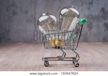 Shopping Cart With Vintage Bulbs On Wooden Surface