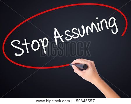 Woman Hand Writing Stop Assuming With A Marker Over Transparent Board
