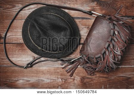 stylish brown bag and hat in wooden background