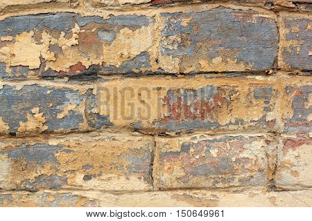 Old brick wall with remnants of yellow and red paint