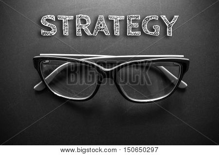 Text strategy with eyeglasses on black background / business concept / dark tone