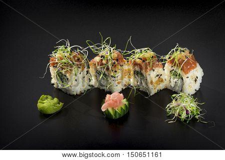 Fresh Uramaki maki Sushi rolls over black background