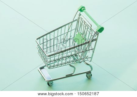 Empty Shopping Cart Over The Green Background