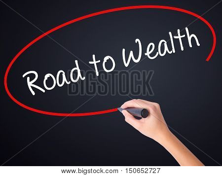 Woman Hand Writing Road To Wealth With A Marker Over Transparent Board