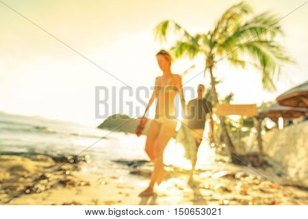 Blurred defocused silhouette of travelers people before sunset - Travel and wanderlust concept with couple at Las Cabanas beach by El Nido Palawan - Warm bright filter - Tilted horizon composition