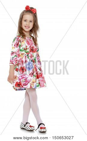 Cute little girl with a long ponytail down to his shoulders, and a red bow on her head, in a beautiful summer dress. Full-length - Isolated on white background
