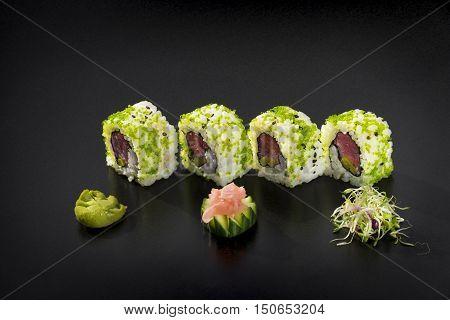 Fresh Uramaki maki Sushi rolls with tuna over black background