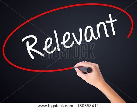 Woman Hand Writing Relevant With A Marker Over Transparent Board