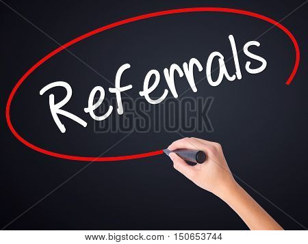 Woman Hand Writing Referrals With A Marker Over Transparent Board .