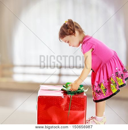 Cute little girl in a pink dress, turned sideways and bent over a large box with a gift. The girl unties the bow.On the background of the great hall of the kindergarten with a semicircular window.
