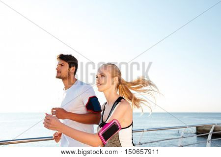 Young sports athletes couple sprinting as part of healthy lifestyle at the pier