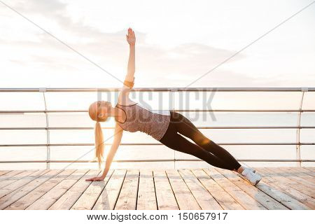 Sporty fitness woman doing planking yoga exercises outdoors at the beach pier