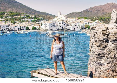 Portrait of adult beautiful woman in straw hat wearing striped top and denim skirt walking on gangway of seafront