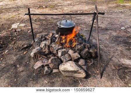 Cauldron hanging on the crossbar over the burning fire